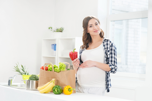 Beautiful pregnant woman in the kitchen with shopping bag and pepper.